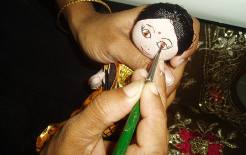 Woman painting eyes on a doll