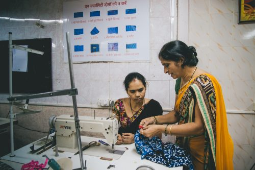 Teaching a trainee to sew at Creative Handicrafts