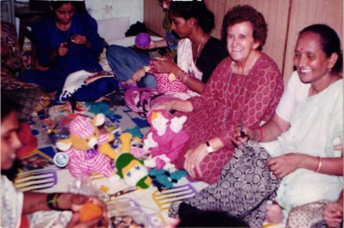 Sister Isabel working with women sewing toys